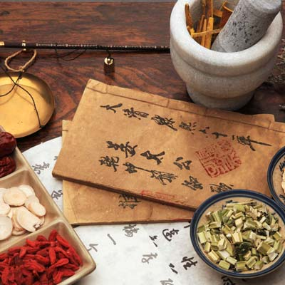 Oriental medicine writing with chinese herbs and mortar and pestle.