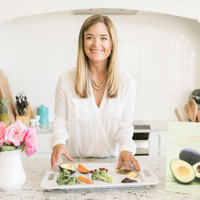 Kathryn Flynn in a kitchen smiling and preparing food for fertility care